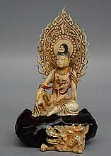 An Oriental polychrome and gilt ivory carved figure of a Buddha and a dragon, mounted on a wooden base, 19thC, H 20 cm