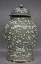 A Chinese celadon vase with cover, decorated with birds and flowers, 19thC, H 61,5 cm (chip on the lid - crack inside the vase)