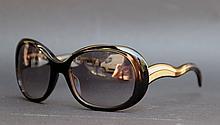 PRADA  Paire de lunettes de soleil, monture en plastique noir et métal, verres noirs.