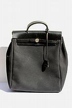 HERMES   Sac Herbag à transformation en toile noire et cuir noir,  accastillage en métal palladié, poignée et lanières en cuir noir, clochette, clef mais manque cadenas.