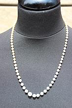 Un collier de perles de culture avec fermoir en platine serti de roses.