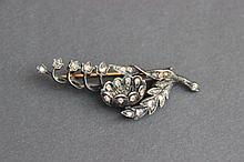 Une broche en or et métal à décor de petites roses.