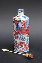 Tabatière en porcelaine à décor de phoenix en rouge et bleu sur fond blanc. Marque dessous.