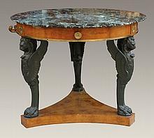 Guéridon circulaire en bois de placage et bois patiné reposant sur trois pieds en forme de bustes de lion.