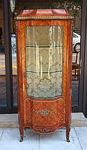 Vitrine en bois de placage ouvrant par une porte.