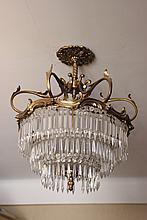 Lustre en bronze ciselé et doré à riche ornementation de pampilles de cristal disposées en trois étages
