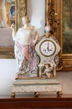 Pendule en porcelaine polychrome ornée d'une figure féminine, d'un coq et d'un putto.