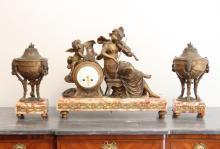 Garniture de cheminée en bronze ciselé et doré composée d'une pendule et de deux cassolettes, à décor allégorique de la musique. Base en marbre.