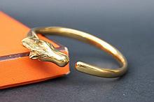 HERMES  Bracelet  jonc en métal plaqué or fermant par une tête de cheval.
