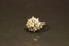 Bague en or blanc ornée d'un diamant central dans un entourage de brillants en forme de fleur.  P : 9 g