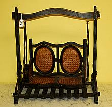 Miniature antique wood and wicker swing.