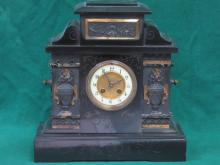 GILDED AND RELIEF DECORATED BLACK SLATE MANTEL CLOCK WITH ENAMELLED DIAL
