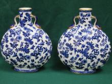 PAIR OF FLORAL DECORATED AND GILDED BLUE AND WHITE CERAMIC FLASKS, APPROXIMATELY 32cm HIGH (AT FAULT)