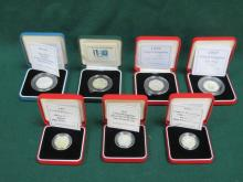 FOUR CASED ROYAL MINT SILVER PROOF 50p COINS AND THREE CASED ROYAL MINT SILVER PROOF £1 COINS