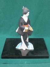 HAKAJA NINGYO DOLL OF A LADY ON A EBONISED STAND.
