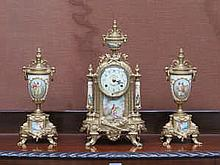 FRENCH STYLE GILT METAL AND PORCELAIN CLOCK AND GARNITURE SET BY FRANZ HERMLE, GERMANY