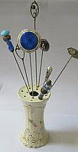 CERAMIC HAT PIN STAND AND EIGHT HAT PINS INCLUDING ONE BY CHARLES HORNER PLUS ONE SILVER AND GOUACHE ENAMELLED, INITIALLED 'LE' LAWRENCE EMANUEL (?)