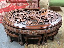 HEAVILY CARVED ORIENTAL STYLE OVAL NEST OF SEVEN TABLES