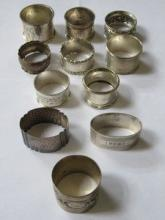 EIGHT SILVER NAPKIN RINGS AND THREE SILVER COLOURE