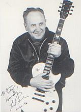 Les Paul. A rare dedicated signed postcard of the guitar legend. Excellent.