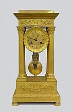 Pendule en bronze doré à colonnes et chapiteau corinthien.                                                                                                    Epoque Empire