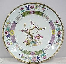Plat en porcelaine blanche à motif floral polychrome et rehaussé d'or.                                                                                  Chine fin XIXème dim 43 cm