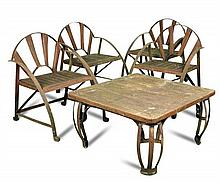 A set of four craftsman made wrought iron framed garden chairs and a low table en-suite,
