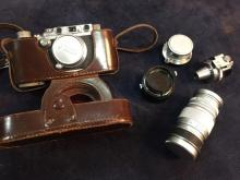 A leather cased 1938 Leica III A camera with three lenses,