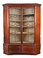 A George III revival concave mahogany corner cupboard, circa 1870