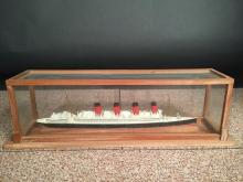 A mid 20th century painted wood model of a four-funnel passenger ship,