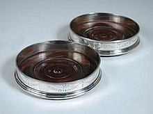 A pair of George III silver wine coasters,