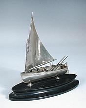 A metalwares model of a sailing dinghy,