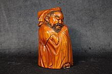 A superb Chinese stained ivory figure of the seated gent, si