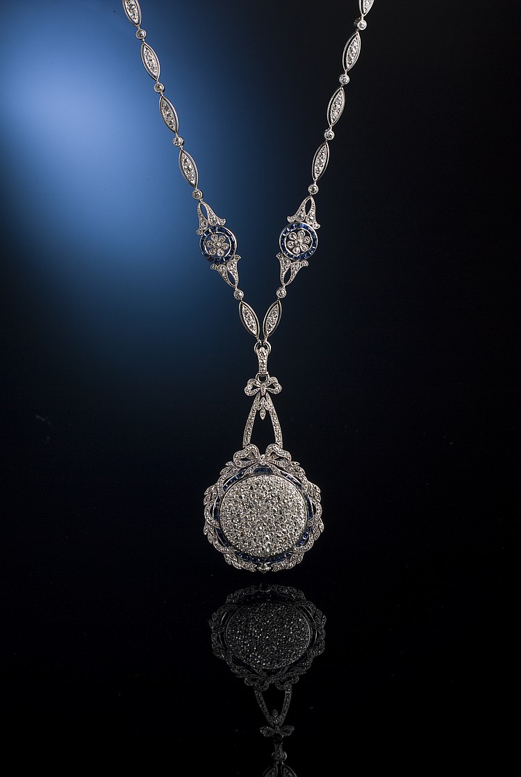 "PLATINUM EDWARDIAN TWO-SIDED DIAMOND AND SAPPHIRE WATCH PENDANT. Authentic. Ca. 1915. Piece contains 496 diamonds with a weight of 10 carats and 82 sapphires weighing approximately 2.25 carats. Signed by the legendary maker ""Black, Starr, & Frost""."