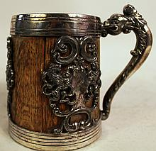 SILVER (PLATE) METAL MOUNTED OAK TANKARD.  Dated 1881-1901.  Heraldic panels and dolphin handle.