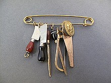 COLLECTION OF SIX PENDANT SIZE CHARMS. Depicting the tools of the butcher's tra de: clevers, saws, knife steels. In gold plate on a gold safety pin with 3