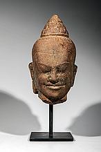 Tête de Shiva coiffée du chignon d' ascète de forme conique le visage exprimant l' intériorité sereine et le sourire de béatitude, les traits et l' expression rappelant l' effigie du roi Javayarman VII.