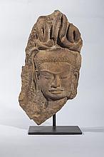 Haut relief de sanctuaire illustré d' une tête de Devata à la chevelure nouée ornée de plumes.