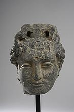 Tête de Boddhisattva au visage serein, , les traits juvéniles empreint de beauté, la moustache frisée, les paupières mi-closes préconisant le regard à l' intérieur de soi, marqué au centre du front de l' urna symbolisant le troisième ?il,