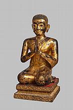 L' adorant Moggalana vêtu de la robe monastique assis sur un tertre quadrangulaire les mains en anjali mudra.