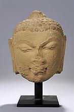 Tête de Bouddha à l' expression juvénile, exprimant la beauté et la sérénité par un sourire de béatitude, coiffée de fines bouclettes, et surmontée de la protubérance crânienne Unisha.