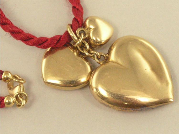 Anhänger: dekorativer, goldener Herzanhänger an rotem Kordelband