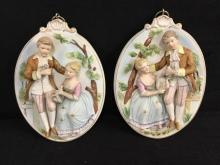 2 vintage oval ceramic hand painted plaques depicting a young man and woman