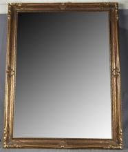 Giltwood and Beveled Mirror, the cove-molded frame decorated with carved scrolls, H.- 46 ½ in., W.- 35 ½ in.