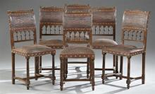 Set of Six French Henri II Style Carved Oak Dining Chairs, late 19th c., the shell carved crest rails over embossed leather backs ab...