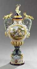 Monumental Capodimonte Covered Vase, 20th c., with putti handles and a Bacchanalian putto on the lid, the side with a large reserve...