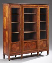 Louis XVI Style Inlaid Mahogany Triple Door Bookcase, late 19th c., the stepped breakfront crown over a central glazed door, flanked...