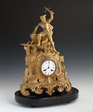French Gilt Spelter Figural Mantel Clock, 19th c., the top with a surmount of a man holding a cross, on a rocky base above an enamel...