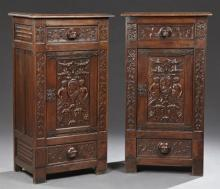Pair of Spanish Renaissance Style Carved Oak Cabinets, early 20th c., the stepped top over a frieze drawer with a lions' head handle...
