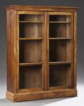French Louis Philippe Carved Walnut Bookcase, 19th c., the stepped crown over two mullioned glazed doors, on a plinth base on flat b...